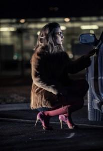 A prostitute next to a car